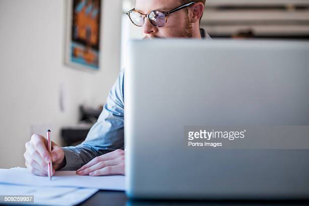Businessman writing notes at laptop desk