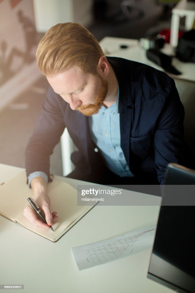 Businessman writing notes in notebook : Stock Photo