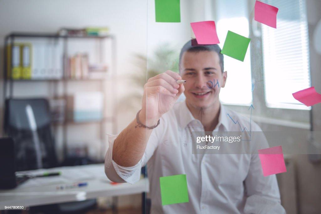 Businessman writing on a glass board : Stock Photo