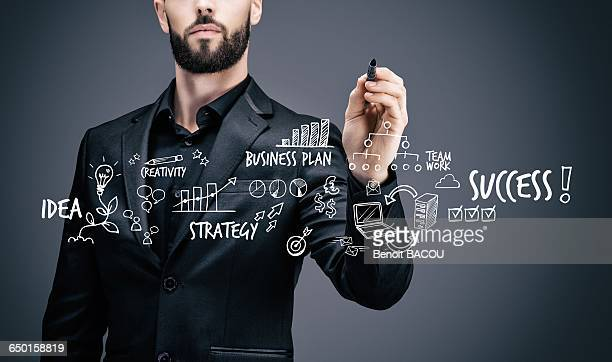 Businessman writing on a virtual table symbols