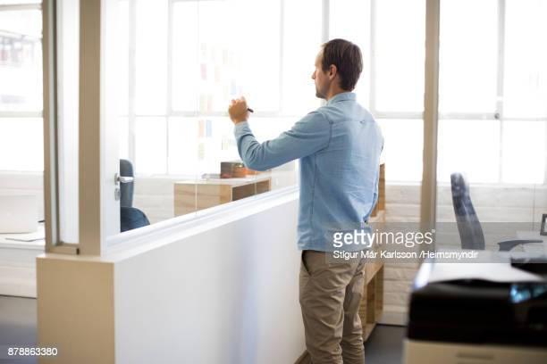 empresário, escrevendo em adesiva nota no escritório - casual chic - fotografias e filmes do acervo