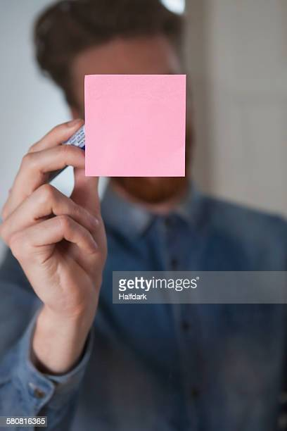 Businessman writing on adhesive note stuck on glass wall