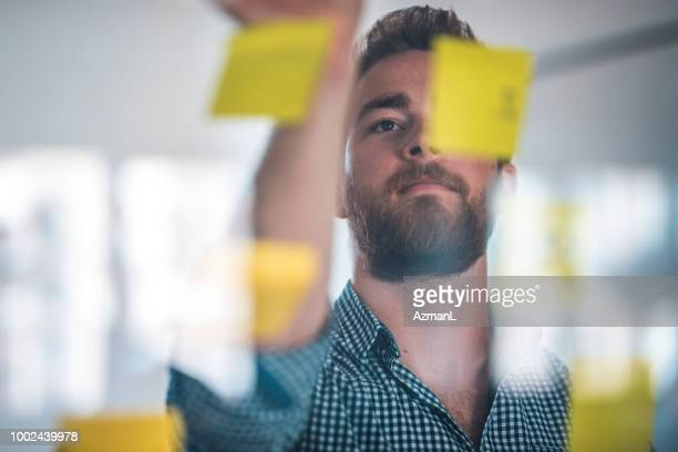 Businessman writing on adhesive notes