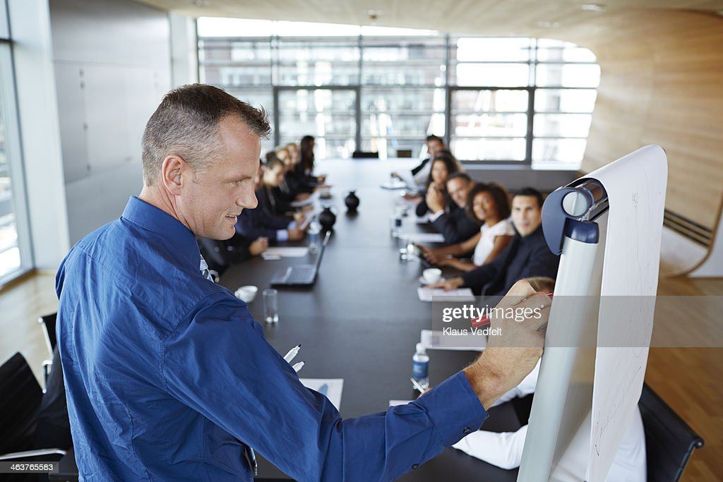 Businessman writing on flipboard at presentation : Stock Photo