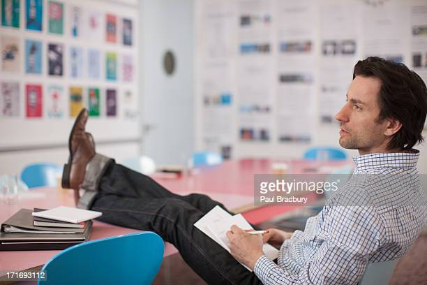 Businessman writing on notepad with feet up in office