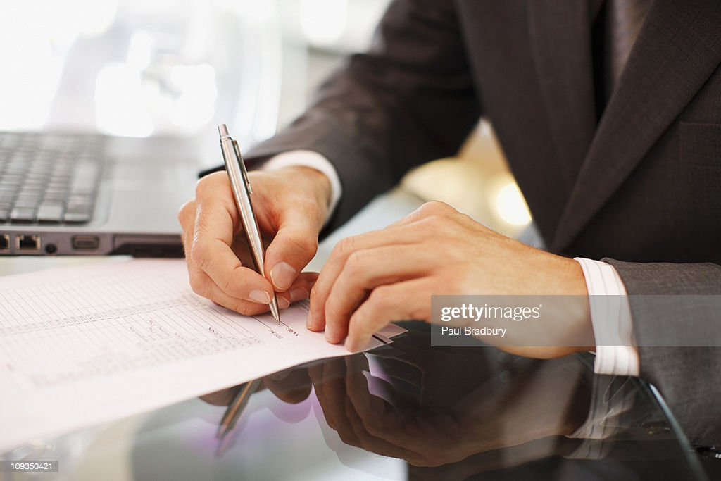 Businessman writing on paper at desk : Stock Photo