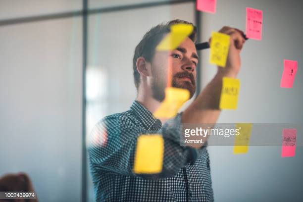 Businessman writing on pink adhesive note
