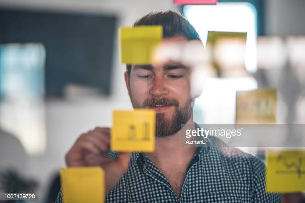 Businessman writing on yellow adhesive note