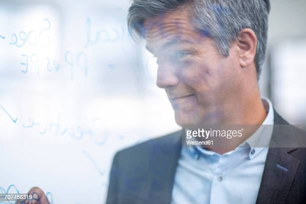 Businessman writing organigram on glass pane, looking confident