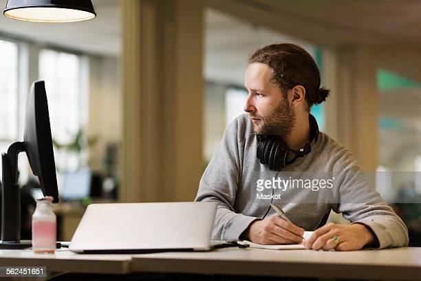 businessman writing while using desktop pc in creative office - solo un uomo di età media foto e immagini stock