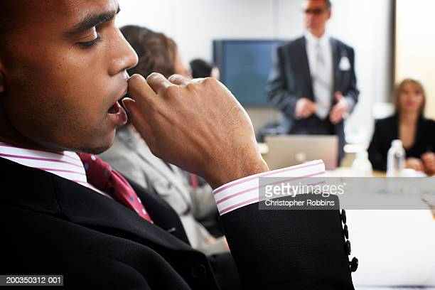 Businessman yawning in meeting, close-up