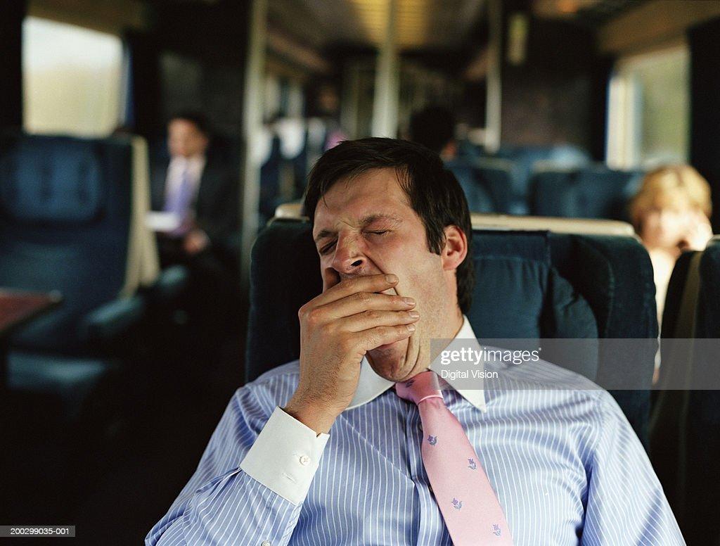 Businessman yawning on train (focus on man) : Foto de stock