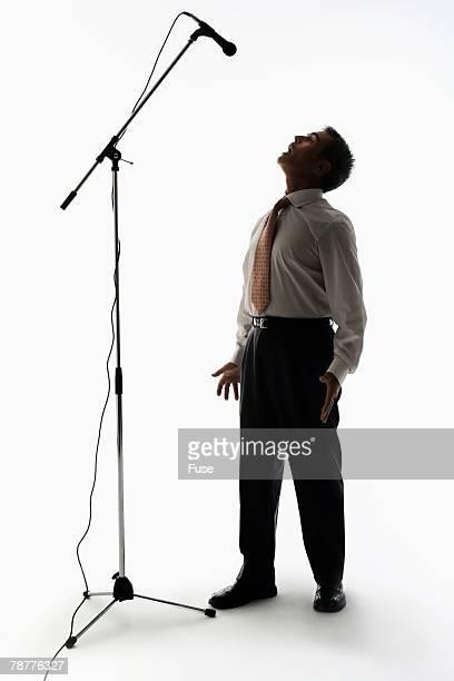 businessman yelling at tall microphone - マイクスタンド ストックフォトと画像