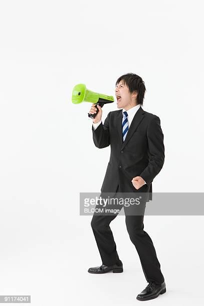 Businessman yelling into megaphone, clenching fist