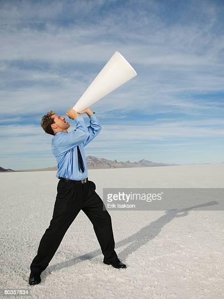 Businessman yelling into megaphone, Salt Flats, Utah, United States