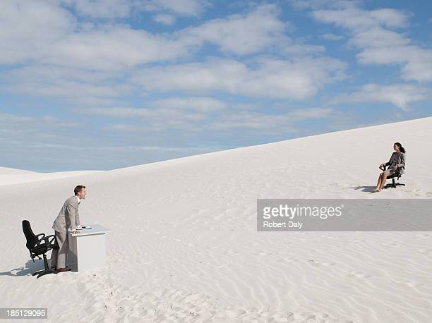 A businessman yelling to a businesswoman in the middle of a desert