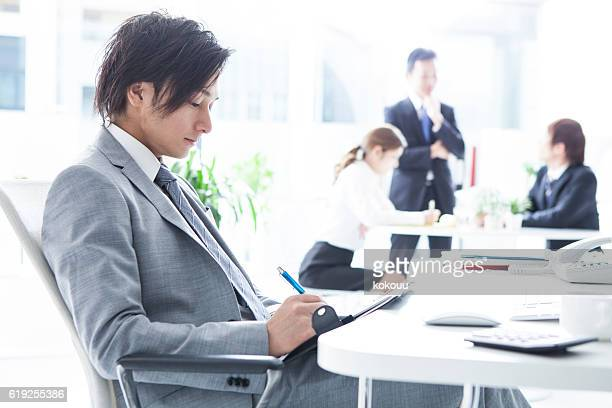 Businessman you are writing a schedule to notebook in office