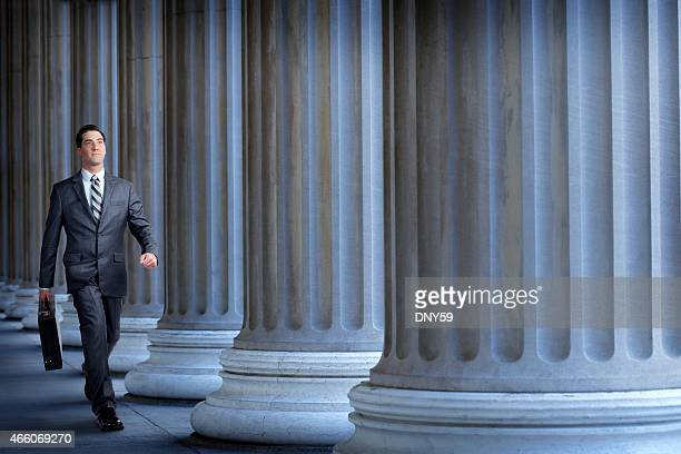 Businessmanor lawyer walking past a row of columns