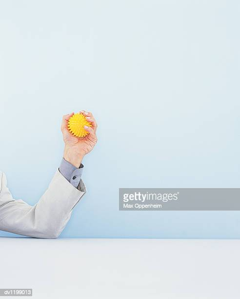 Businessman's Arm Gripping a Desk Toy For Stress