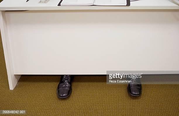 Businessman's feet under desk