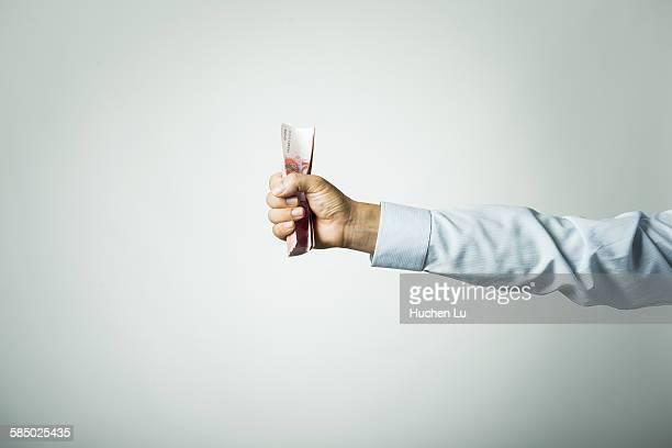 Businessman's hand holding chinese money