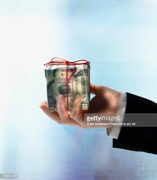 Businessman's hand holding gift box made of US hundred dollar bills