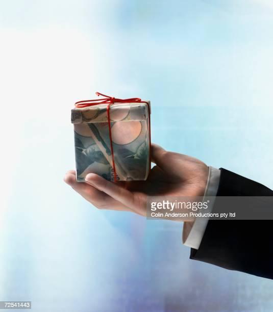 Businessman's hand holding gift box made of Yen
