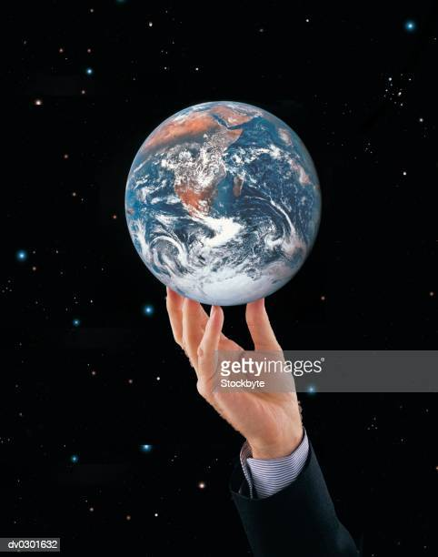 businessmans hand holding up earth or globe, starry background - world at your fingertips stock pictures, royalty-free photos & images