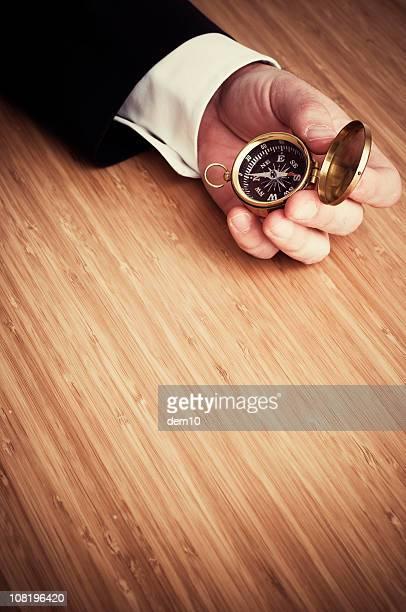 Businessman's Hand am Schreibtisch hält Compass