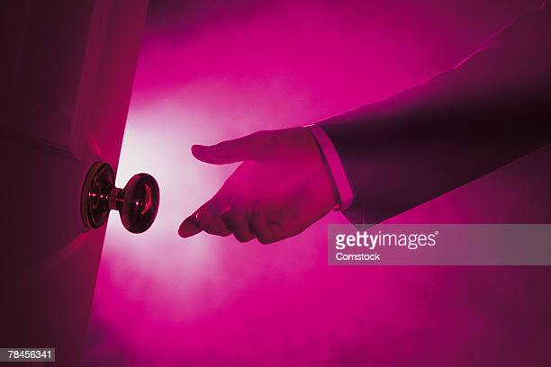 Businessman's hand reaching for door