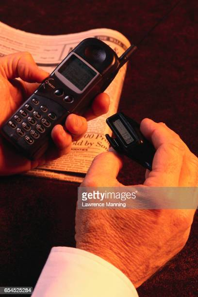 Businessman's Hands Holding Cell Phone and Pager