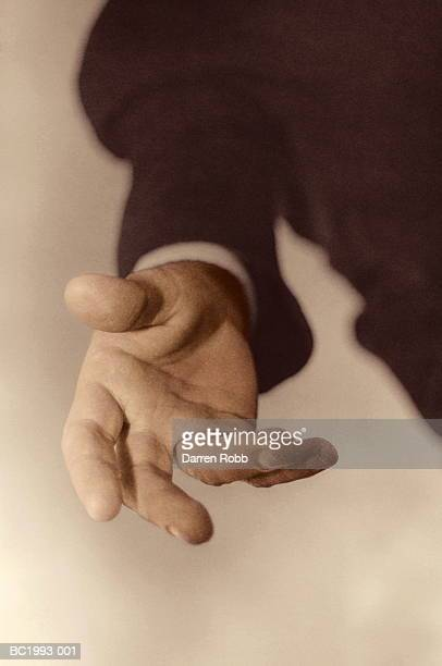 Businessman's outstretched hand, close-up (tinted B&W)