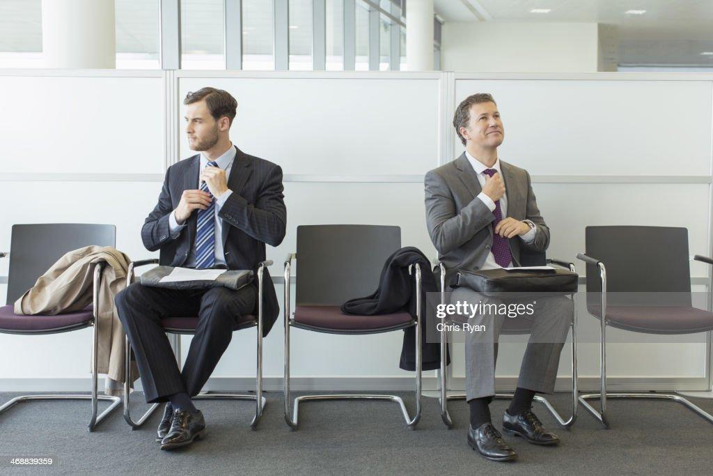 Businessmen adjusting ties in waiting area : Stock Photo