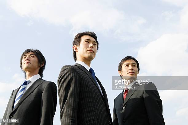 Businessmen against blue sky, portrait, close-up