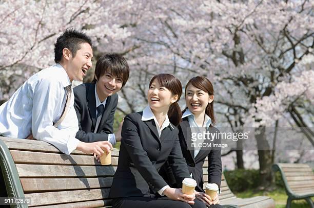 Businessmen and businesswomen enjoying talking at bench