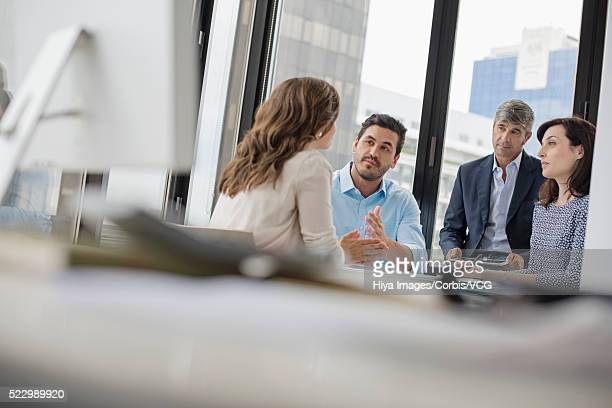 Businessmen and businesswomen having discussion at table