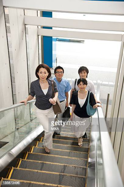 Businessmen and businesswomen in business casual getting on escalator