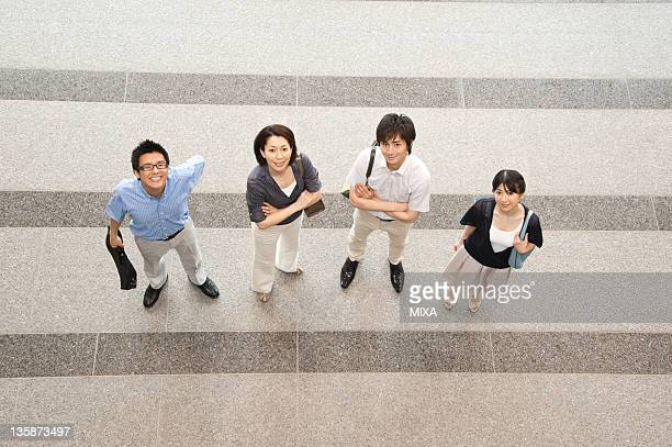 Businessmen and businesswomen in business casual looking up at lobby of building