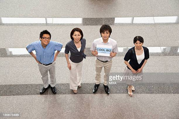 Businessmen and businesswomen in business casual standing and showing board