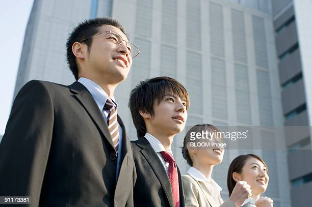 Businessmen and businesswomen smiling, looking upward