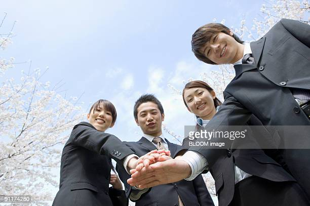 Businessmen and businesswomen smiling with hands together