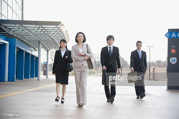 businessmen and businesswomen walking in front of building - 隣り合わせ ストックフォトと画像