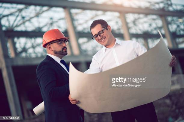 Businessmen and Construction Worker Checking Blueprints