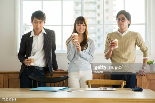 Businessmen and woman drinking coffee in office