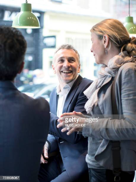 Businessmen and woman having discussion in restaurant