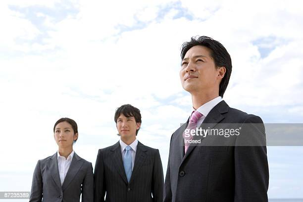 Businessmen and woman looking away