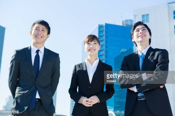 Businessmen and woman looking up, smiling
