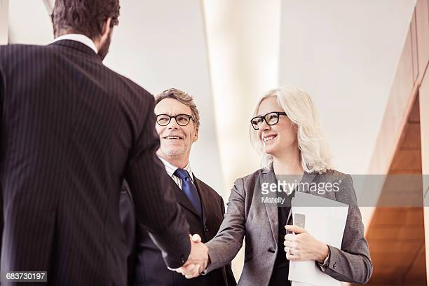 Businessmen and woman shaking hands in office corridor