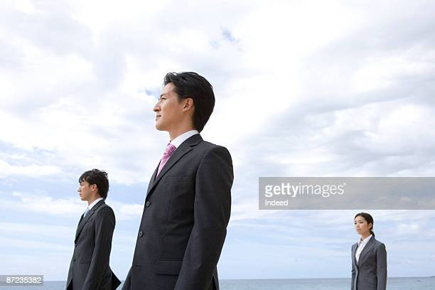 Businessmen and woman standing on beach