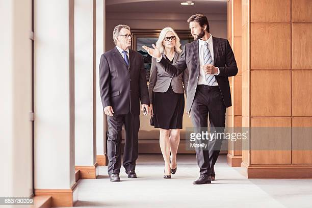 Businessmen and woman walking and talking in office corridor